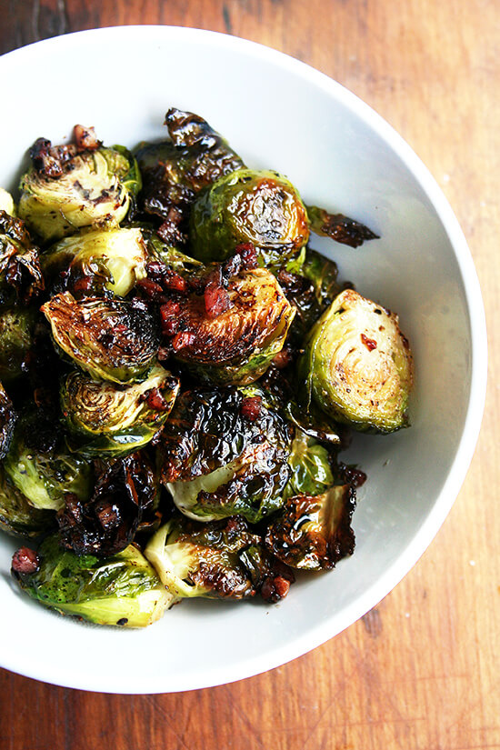 Close-up overhead view of brussel sprouts roasted with olive oil, salt and pepper, and crispy pancetta in a small white serving bowl.