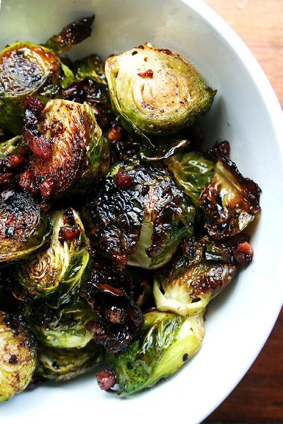 Overhead close-up of brussel sprouts roasted with olive oil, salt and pepper, and crispy pancetta in a white serving bowl.