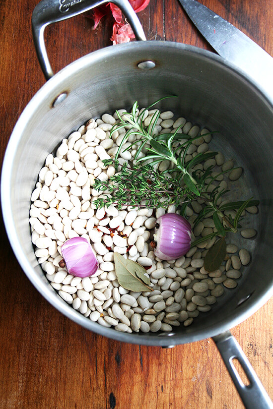 A pot filled with dried white beans, herbs, a bay leaf, and half a shallot.
