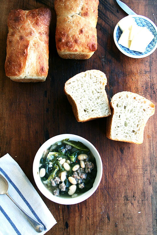 A bowl of white bean, sausage, and escarole soup aside  homemade peasant bread.