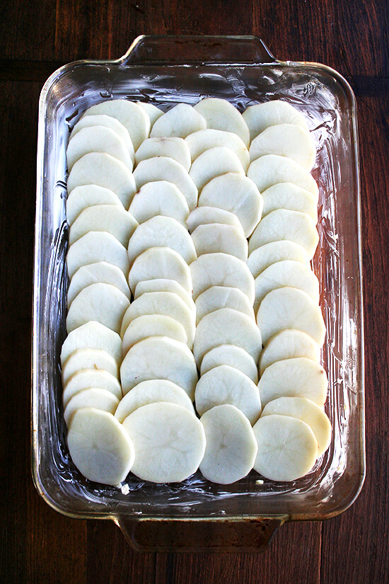 A 9x13-inch baking dish with one layer of sliced potatoes.