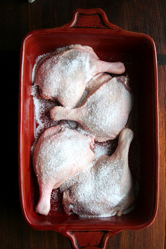 Four duck legs in a 9x13-inch red baking dish sprinkled with salt.