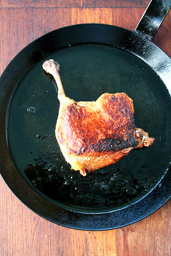 A seared duck leg confit in a cast iron skillet.
