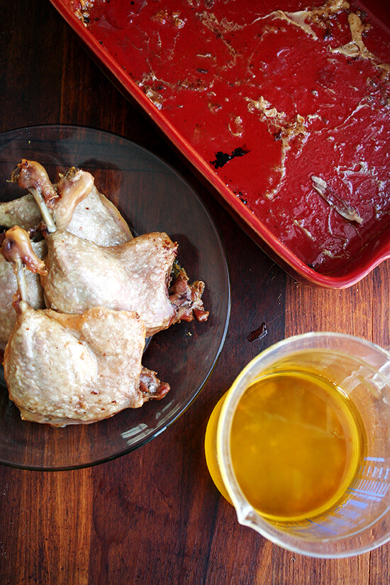 Four duck leg confits on a plate aside a liquid measure filled with rendered fat.
