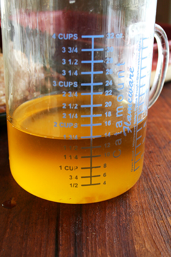 A liquid measure filled with rendered duck fat and butter.