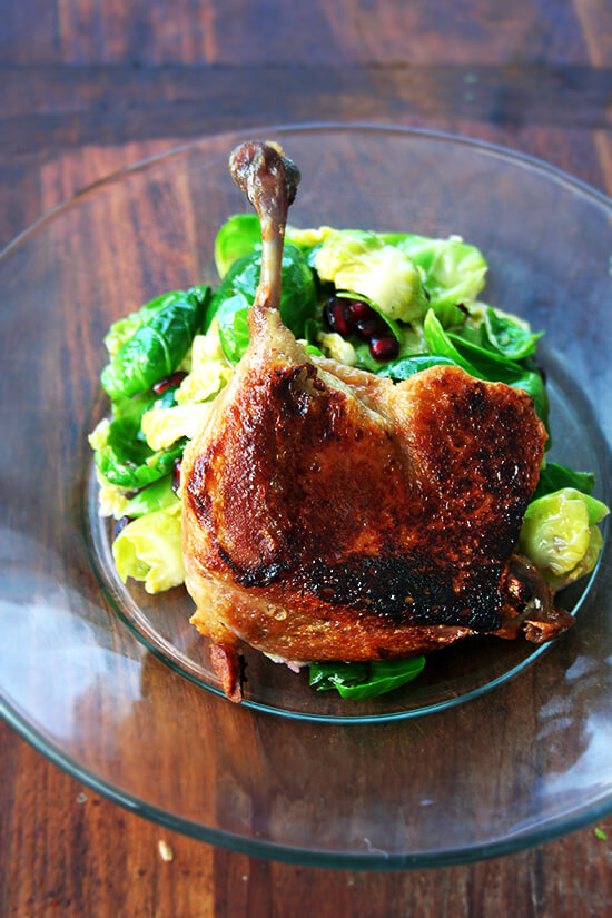 A duck leg confit standing up on a plate supported by a mound of salad greens.