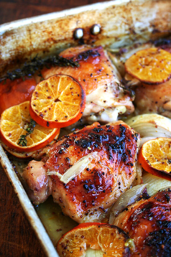 A roasting pan with roast chicken and clementines.