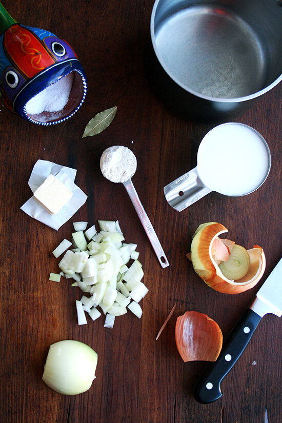 bechamel ingredients on a boardL onion, butter, flour, salt, milk, bay leaf.