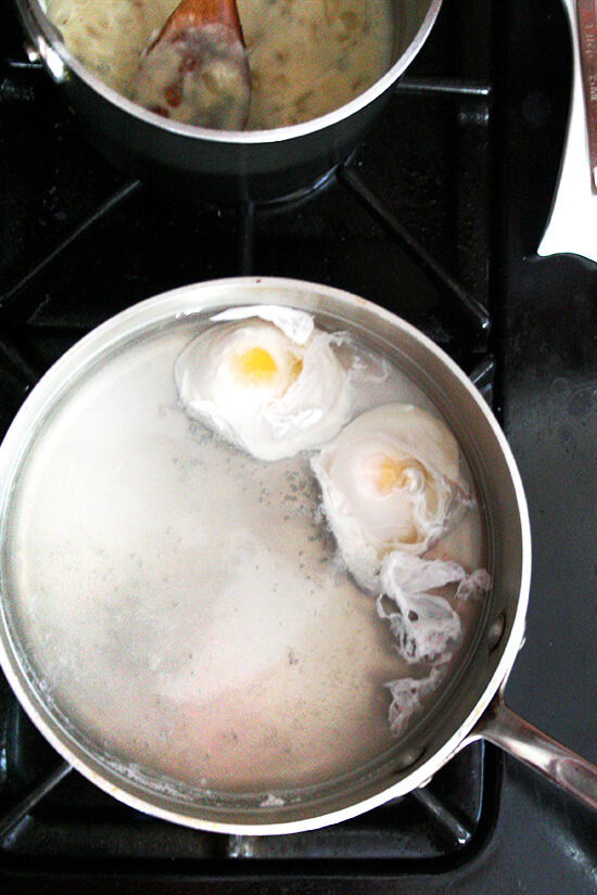 Two eggs poaching in a pot on the stovetop.