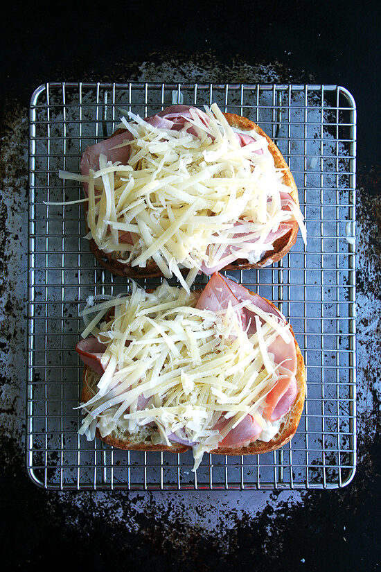 Croque monsieur in the making: Two slices of toast topped with béchamel, ham, and cheese on a rack set on a sheet pan.