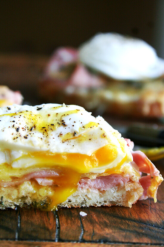 Croque madame — croque monsieur topped with a poached egg — on a cutting board.