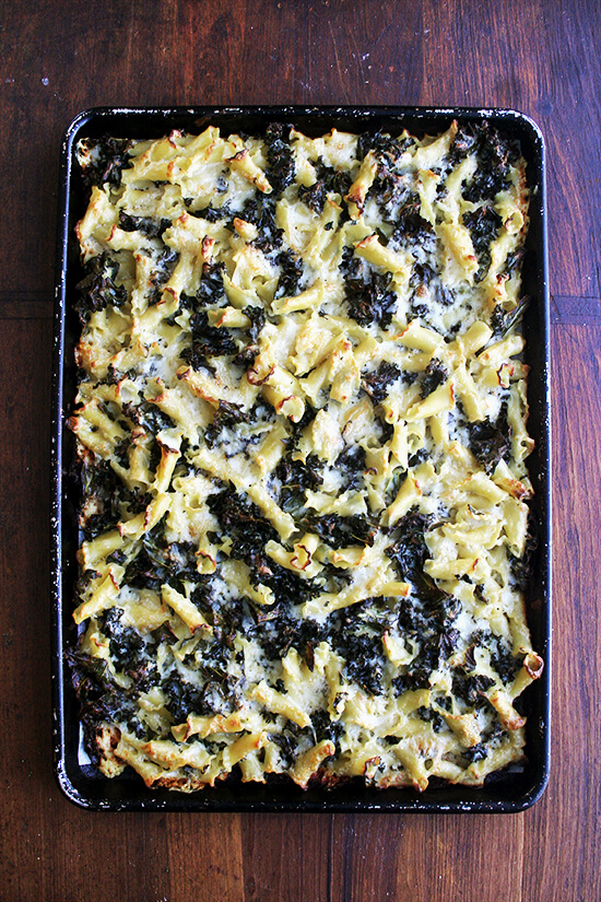 An overhead shot of just-baked pasta gratin with kale on a sheet pan.