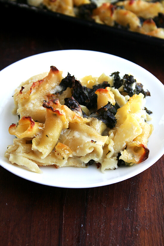 A portion of sheet pan pasta gratin with kale on a plate.