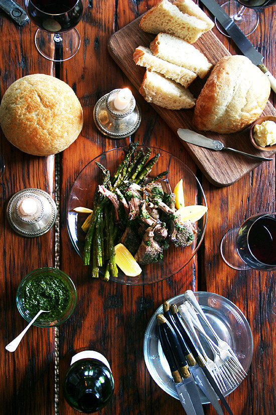 An overhead shot of a dinner with homemade bread, mint sauce, broiled lamb chops, and red wine.