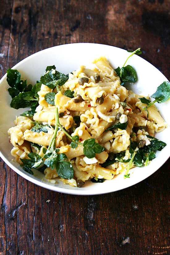 In this campanelle dish, a warm anchovy-caper-olive oil sauce dresses the pasta first; then a splash of lemon juice and reserved cooking liquid thin out the sauce ensuring it coats the pasta nicely; finally chopped hard-boiled eggs and greens complete the dish to make an impromptu, deeply satisfying dinner. // alexandracooks.com