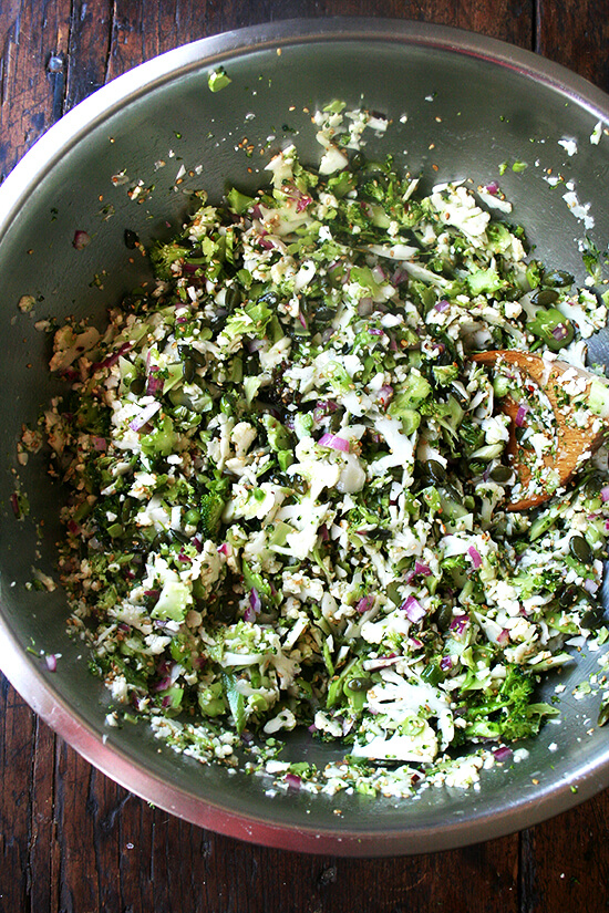 A large bowl of broccoli - cauliflower salad all tossed together.