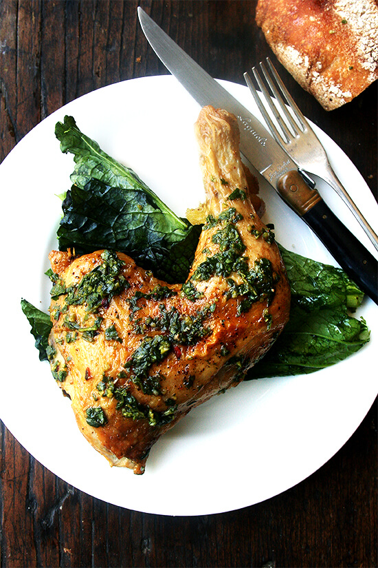 A plate of crispy roast chicken with herb sauce.