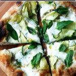 A summer squash pizza cut into quarters.