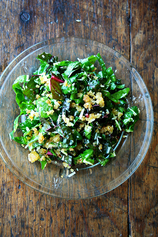 A plate of Swiss chard salad with bread crumbs, parmesan and a lemon dressing.