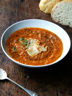A bowl of roasted tomato and bread soup aside homemade bread and a spoon.