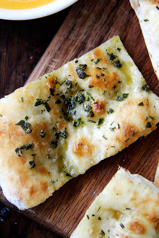Just-baked herbed flatbread cut into slices on a board.