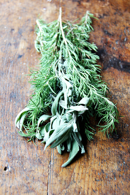 A few sprigs rosemary and sage on a board.
