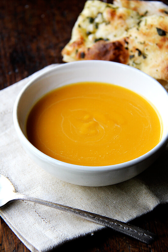A bowl of butternut squash and cider soup with a spoon.