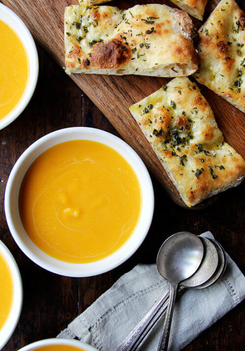 Bowls of butternut squash and cider soup aside herbed flatbreads.