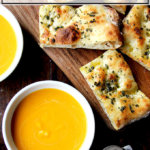Butternut squash soup in bowls aside herbed flatbreads.