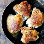 Crispy chicken thighs with preserved lemon in a skillet.