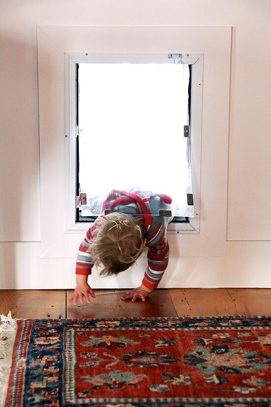 Child climbing through dog door.