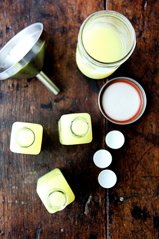 An overhead shot of glass jars filled with homemade limoncello plus a funnel.
