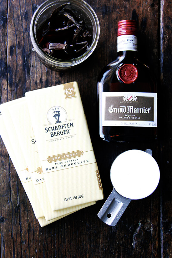 Ingredients for boozy chocolate truffles on a table: chocolate bars, cream, vanilla beans, and Grand Marnier.