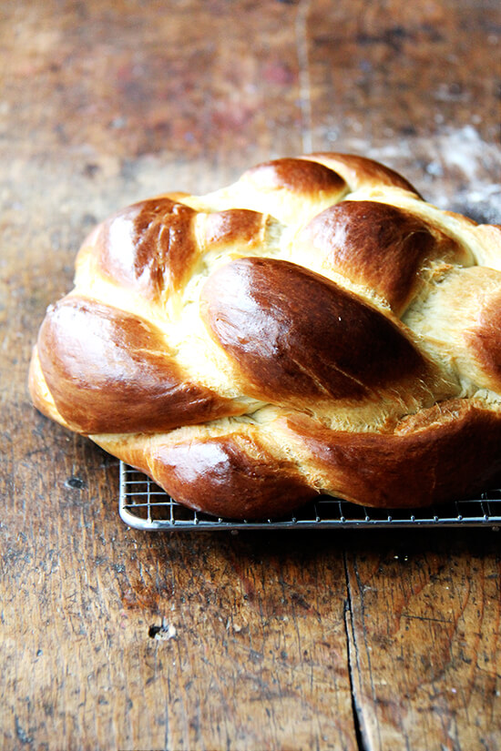 A challah bread round on a cooling rack.
