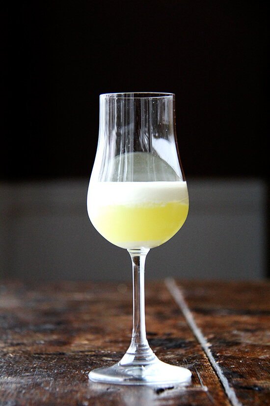 A glass filled with homemade limoncello topped with heavy cream.