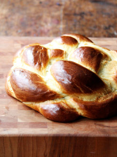 A loaf of challah bread on a cutting board.