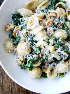 A bowl of pasta with brown butter, swiss chard and walnuts.