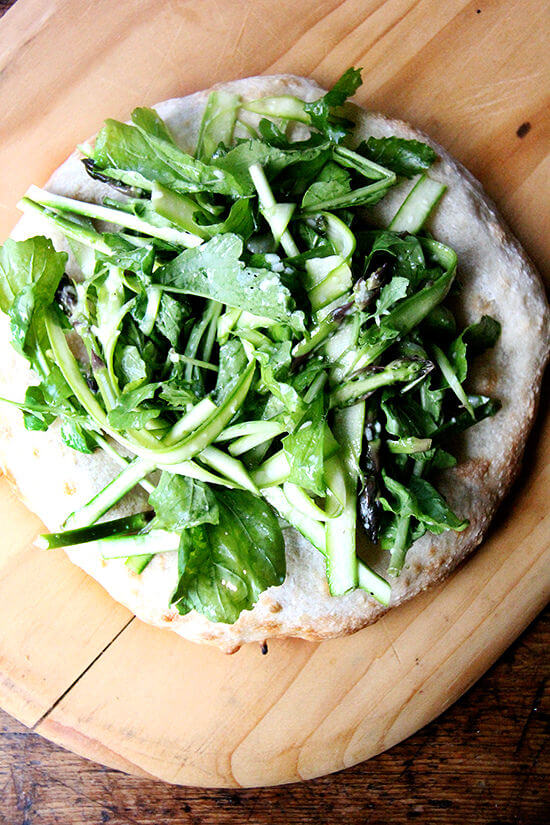 This shaved asparagus arugula salad makes a lovely side dish on its own, but can easily be turned into a filling and delicious meal: Simply heap it atop an enormous carbohydrate—pizza, flatbread, bruschetta. There's no science behind that. // alexandracooks.com