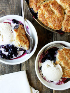 Bowls of blueberry cobbler with ice cream on a table.