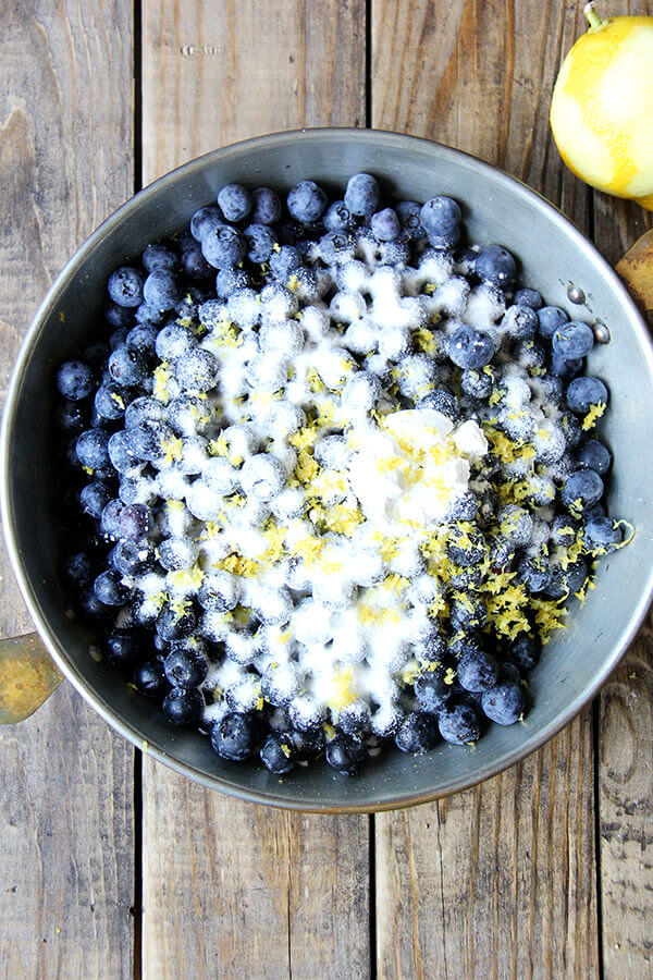 Step 2 of blueberry cobbler recipe: coat berries with sugar and lemon zest.