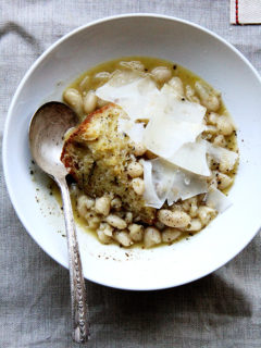 A bowl of stewy white beans with bread and parmesan.