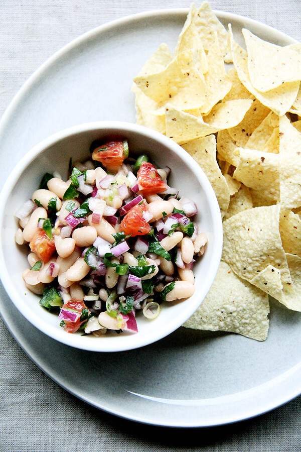A bowl of white bean salsa aside chips.