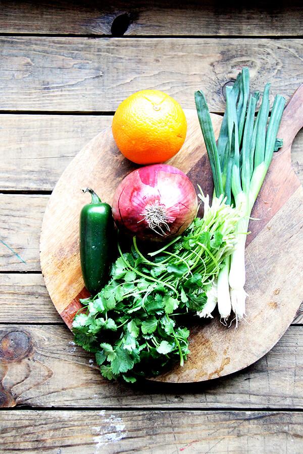 A board of cilantro, red onion, orange, scallions, and jalapeno.