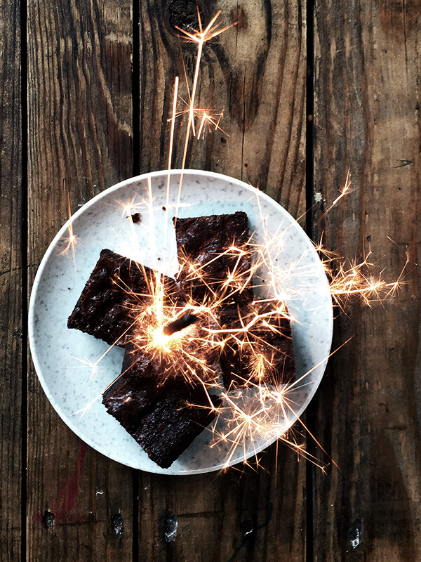 The best ever, rich fudgy brownie recipe on a plate with sparklers lighting off on top of them.