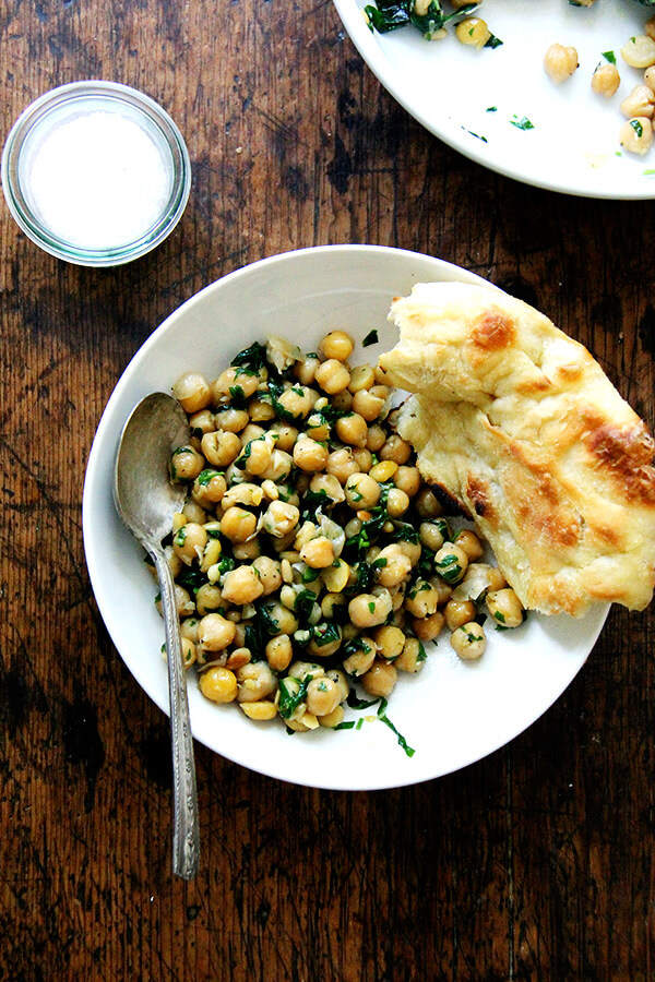 This recipe for chickpea saute with basil and pine nuts is inspired by the beautiful basil that has been arriving in our CSA: sweat garlic in extra-virgin olive oil, add cooked chickpeas, toasted pine nuts, and lots of salt, pepper, and chopped basil; sauté briefly; and serve immediately. Last Friday evening, a few friends came over for dinner, and we ate these chickpeas with grilled whole Branzino, focaccia, and a simple salad — it was a nice summer meal. // alexandracooks.com