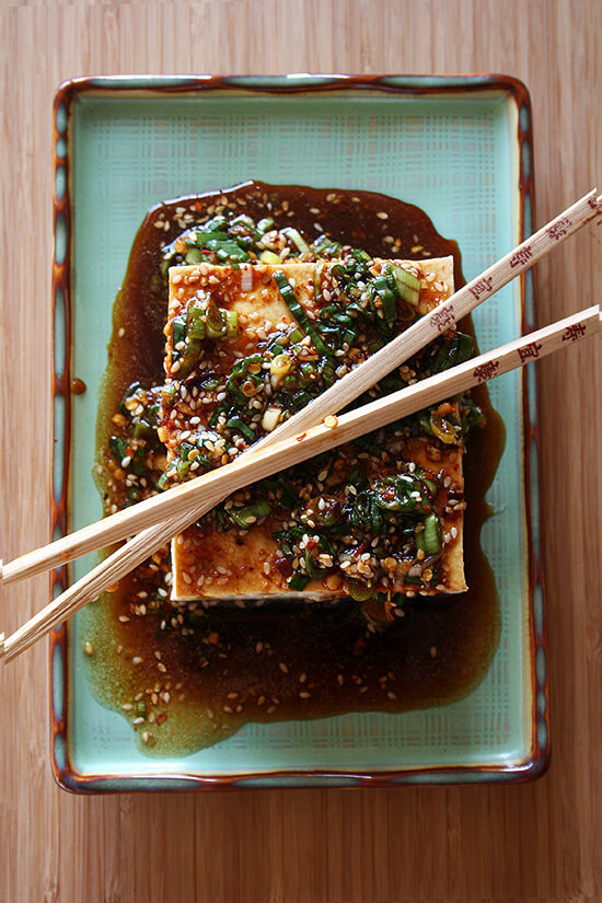 A block of warm tofu with spicy sesame scallion sauce on a plate.