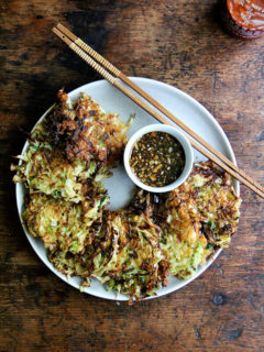 A plate of okonomiyaki with soy dipping sauce.