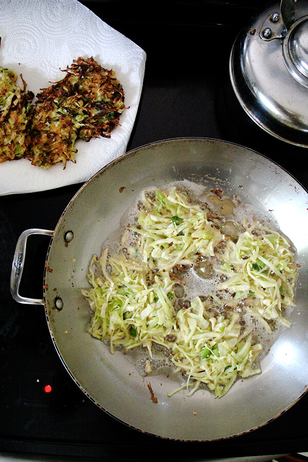 frying the cabbage pancakes in a large skillet