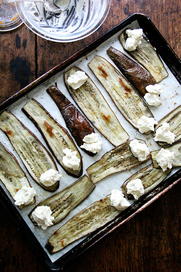 Roasted eggplant on a sheet pan with dollops of ricotta on each end, ready to be rolled.