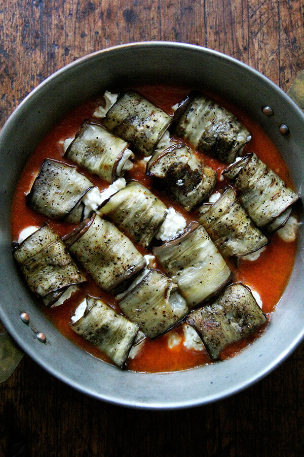 Eggplant involtini in a baking dish with tomato sauce.